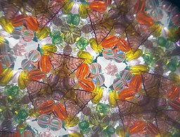 """Rotational symmetries in designs produced by a kaleidoscopeDSCN2440"""" src=""""https://upload.wikimedia.org/wikipedia/commons/thumb/1/19/Rotational_symmetries_in_designs_produced_by_a_kaleidoscopeDSCN2440.jpg/512px-Rotational_symmetries_in_designs_produced_by_a_kaleidoscopeDSCN2440.jpg"""">"""